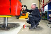 foto of bender  - Mechanic repainting a forklift on a bridge in a workshop - JPG