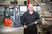 Tough looking mechanic, holding a large wrench, posing in front a forklift in a garage