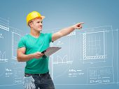 repair, construction and maintenance concept - smiling man in helmet with clipboard pointing finger