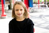 picture of tween  - Caucasian tween girl outdoors, smiling and happy.