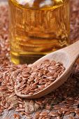 stock photo of flax seed oil  - Flax seed in a wooden spoon and a bottle with oil - JPG