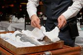 stock photo of crust  - Waiter is carving fish baked in salt crust by restaurant table - JPG