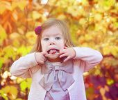 young girl sticking out her tongue in front of autumn orange leaves
