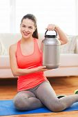 fitness, home and diet concept - smiling teenage girl with jar of protein at home
