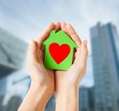 charity, real estate and family home concept - closeup picture of female hands holding green paper h