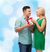 happiness, holidays, celebration and couple concept - smiling couple with gift box