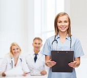 healthcare and medicine concept - smiling female doctor or nurse with clipboard and stethoscope