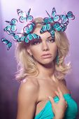 Luxury young girl with butterflies on her head. Beautiful stylish trendy woman.
