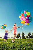 Beautiful little girl with mother colored balloons and rainbow umbrella holding  in  the park. Smili