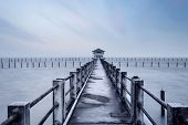 a long pier leading out onto the sea