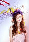 foto of headgear  - Colorful portrait of attractive woman with feathers and headgear looking at camera - JPG