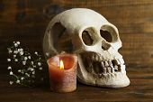 Skull and candle on wooden background