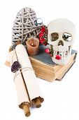 Skull, wicker heart and dried roses on old book isolated on white. Conceptual photo of love magic