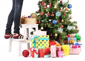 Female legs on wooden ladder near Christmas tree and gifts isolated on white