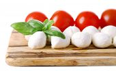 Tasty mozzarella cheese balls with basil and red tomatoes, on cutting board, isolated on white