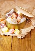 Sweet candies in metal can, on wooden background