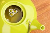 Teapot with chamomile tea on wooden table close-up