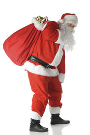 stock photo of santa claus hat  - Santa Clause carrying a sack heavy with children - JPG
