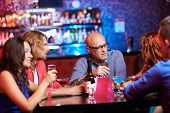 stock photo of gathering  - Friendly people with drinks gathered in the bar - JPG