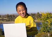 foto of mongolian  - Mongolian girl with laptop by lake - JPG