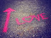 picture of instagram  - a pink arrow showing the way to love written on a sidewalk with chalk toned with a retro vintage instagram filter effect  - JPG