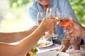 stock photo of lunch  - Closeup of wine glasses held by family at lunch - JPG
