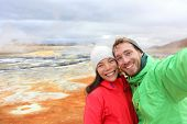 Iceland tourists couple taking selfie photo with smartphone camera at landmark destination: Namafjall Hverarondor hverir mudpot also called mud pool hot spring or fumarole. Beautiful Icelandic nature. poster