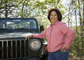 pic of four-wheel drive  - Senior woman leaning on jeep in woods - JPG