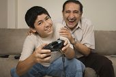 pic of grandfather  - Hispanic grandfather laughing while grandson plays video game - JPG