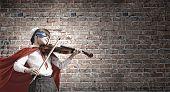 picture of violin  - Cute girl of school in superhero costume playing violin - JPG