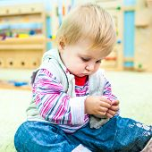 pic of playgroup  - little girl in the classroom early development plays with bright toys - JPG