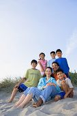image of nuclear family  - Portrait of Hispanic family sitting on beach - JPG
