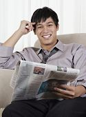 picture of pacific islander ethnicity  - Young Pacific Islander businessman reading newspaper - JPG