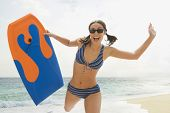 pic of boogie board  - Woman running on beach with boogie board - JPG