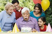 foto of mother law  - Senior Hispanic man blowing out birthday candles with family in park - JPG