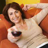 stock photo of differential  - Hispanic woman pointing remote control - JPG
