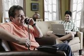 stock photo of pre-adolescent child  - Hispanic father and son relaxing in livingroom - JPG