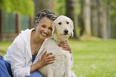 stock photo of adults only  - African American woman hugging dog - JPG