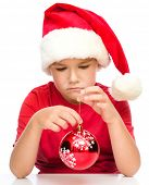 image of sad christmas  - Young unhappy girl in santa cloth is holding a christmas decoration - JPG