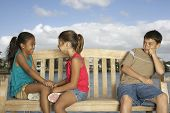 stock photo of pre-adolescent child  - Mixed Race children on bench - JPG