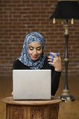 stock photo of burka  - Middle Eastern businesswomen looking at laptop - JPG