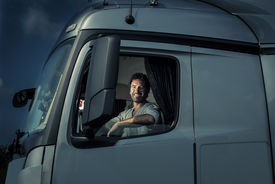 foto of truck-stop  - Truck driver sitting in cab - JPG