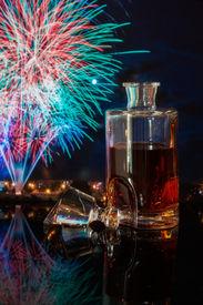 stock photo of debauchery  - bottle of whiskey on a background of fireworks - JPG