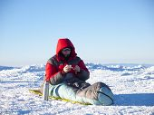 image of thermos  - A man sits in a sleeping bag and drinking tea from a thermos on the background of the winter mountains - JPG