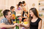 image of social housing  - Young couple at a house party sit on the floor and knocking with drinks in the background you can see their friends two couples - JPG