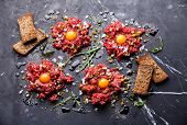 picture of tartar  - Beef tartare with pickled cucumber and fresh onion on dark marble background - JPG