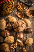 stock photo of nutcracker  - steel nutcracker and nuts of various kinds nuts in honey - JPG