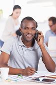 picture of people talking phone  - Handsome young African man talking on the mobile phone and smiling while people working on background - JPG