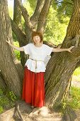 foto of woman red blouse  - European woman with shot brown hair in red skirt and white blouse walking in park standing near willow trees.