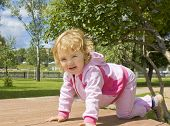 stock photo of creeping  - Little child girl Caucasian creeping on knees on walk outdoors - JPG
